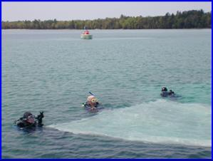 Scuba Divers place a benthic barrier in Higgins Lake